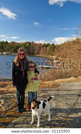 Sisters with dog in outdoor portrait - stock photo