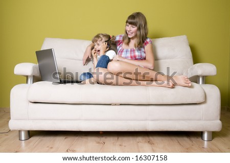 Sisters with laptop on sofa - stock photo