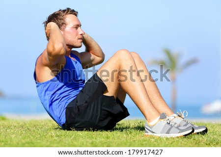 Sit-ups - fitness man training sit up outside in grass in summer. Fit male athlete working out cross training exercising. Caucasian muscular sports model in his 20s. - stock photo