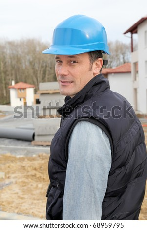 Site supervisor with security helmet standing on construction site - stock photo