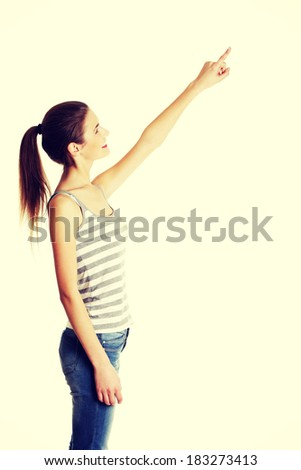 Site view portrait of a beautiful young female caucasian teen pointing up with her finger - stock photo