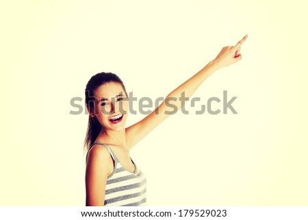 Site view portrait of a beautiful young female caucasian teen pointing up with her finger and smiling to the camera, on white. - stock photo