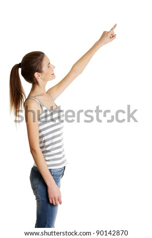 Site view portrait of a beautiful young female caucasian teen pointing up with her finger, on white. - stock photo