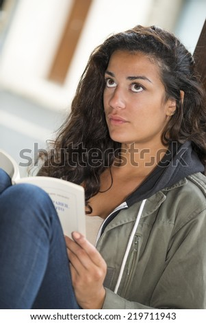 Sitting against a wooden post, a young woman (20s) reading a book outdoors. Now she is looking up. Closeup - stock photo