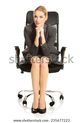 Sitting businesswoman with hands on chin. - stock photo