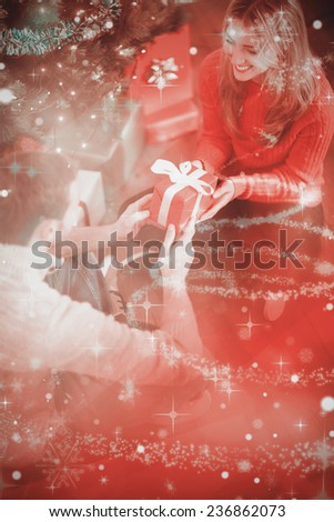 Sitting couple giving each other presents against glittering christmas tree design - stock photo