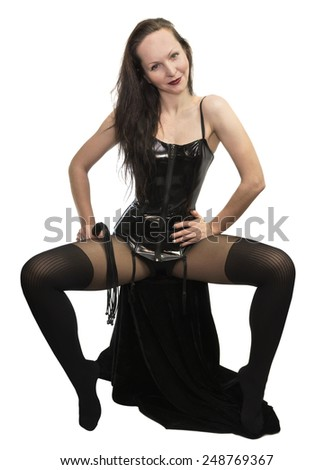 Sitting girl wearing erotic black costume and holding lash, beautiful woman in leather underwear isolated on white - stock photo