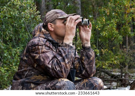 sitting hunter  looks through the binoculars - stock photo