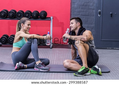 Sitting muscular couple talking together while drinking water - stock photo