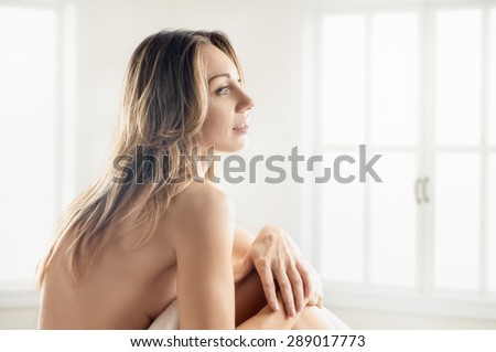 sitting nude lady in a white room about window. back to camera - stock photo