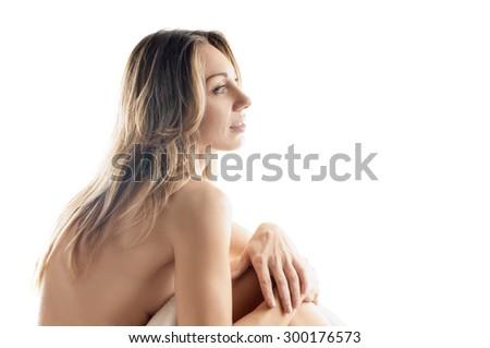 sitting nude lady on bed on white background. back to camera - stock photo