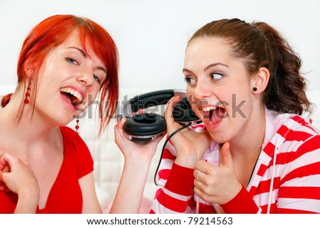 Sitting on sofa two cheerful young girlfriends holding headphones and listening music together - stock photo