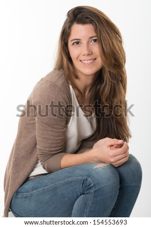 Sitting portrait of a cute expressive young woman - stock photo