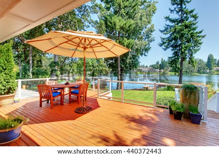 Sitting room area on walkout deck with patio table, umbrella and chairs overlooking water view. - stock photo