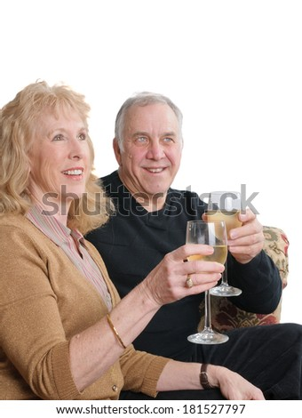 sitting Senior couple toasting someone with a glass of wine, isolated on white - stock photo