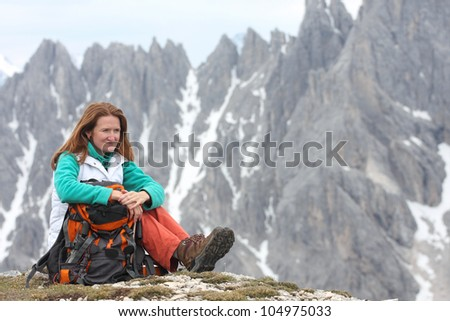 sitting smiling girl with the high rocky mountains at the background - stock photo