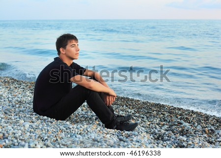 sitting teenager boy on stone seacoast, Looking afar - stock photo