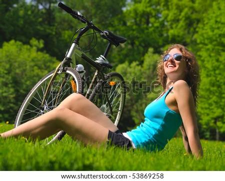 sitting woman near her bike in park - stock photo