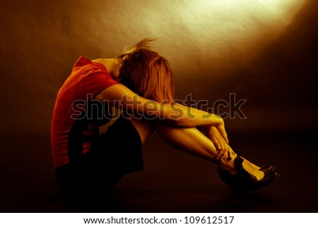 sitting woman on a dark background - stock photo