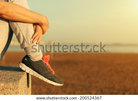Sitting Woman's feet in a sneakers. - stock photo