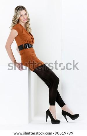 sitting woman wearing dress and black boots - stock photo