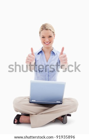 Sitting woman with laptop giving thumbs up against a white background - stock photo