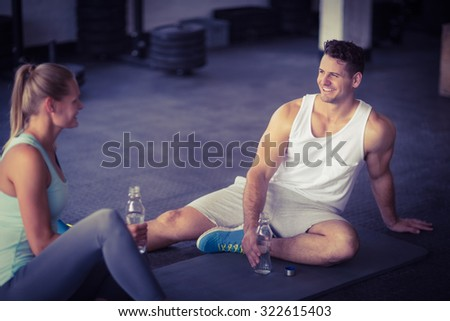 Sitting young couple drinking water together in crossfit gym - stock photo