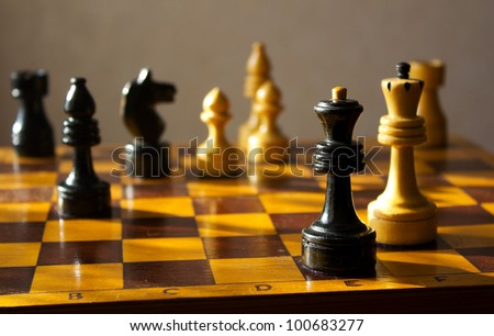 situation on chessboard with black queen and white king - stock photo