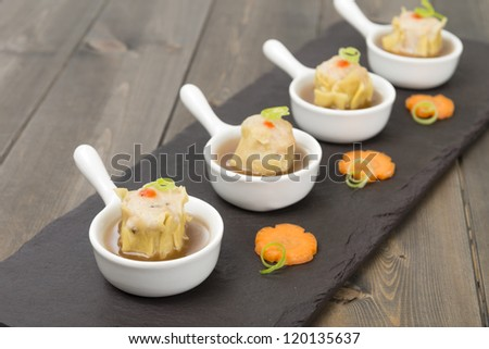 Siu Mai  - Chinese steamed pork dumplings in sauce. - stock photo