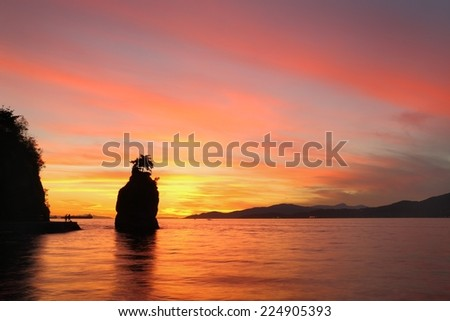 Siwash Rock Sunset, Stanley Park, Vancouver. Sunset over English Bay silhouetting Siwash Rock in Stanley Park. Vancouver, British Columbia, Canada.  - stock photo