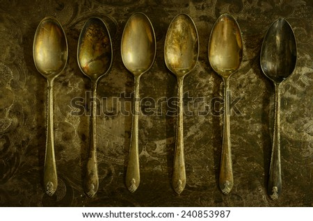 Six antique teaspoons lined up on a tarnished, engraved vintage tray - stock photo