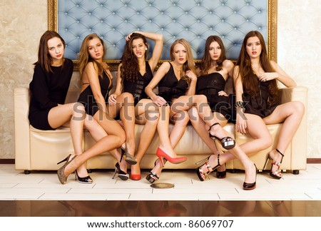 Six beautiful sexy models are sitting on the sofa - stock photo