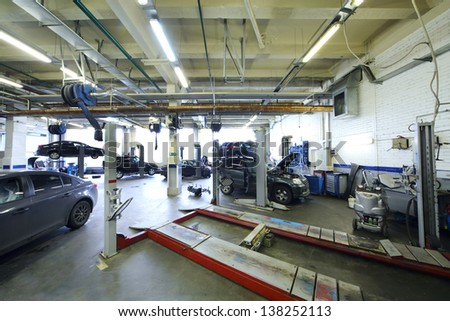 Six black cars stand in garage with special equipment for repair. - stock photo