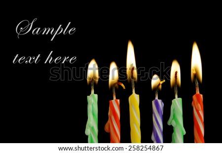Six burning birthday candles on black background  - stock photo