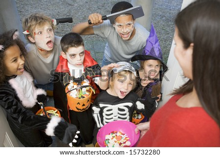 Six children in costumes trick or treating at woman's house - stock photo