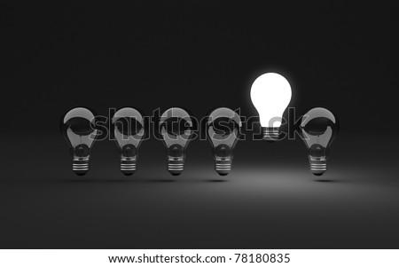Six clear light bulbs, one illuminated - stock photo