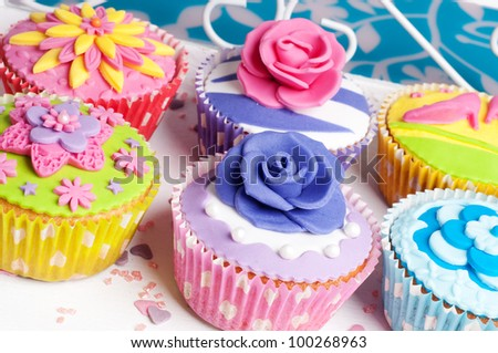 Six colorful spring cupcakes with floral decoration - stock photo