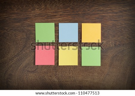 Six colorful sticky notes on wooden background - stock photo