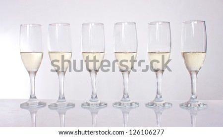 six crystal glasses of wine standing in a row - stock photo