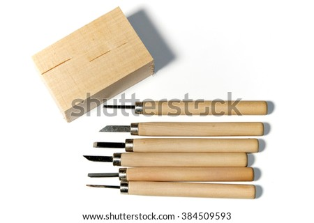 Six different wood carving tools and a block of basswood, over white, not isolated - stock photo