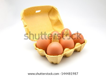 Six eggs in carton isolated on white - stock photo