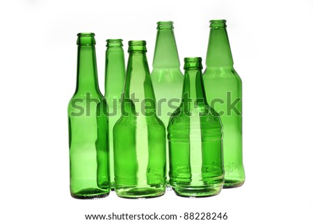 six empty glass green bottles of different size over white background/green empty beer bottles - stock photo