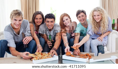 Six friends eating pizza in the living-room on the sofa - stock photo
