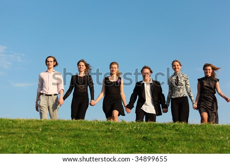 Six friends go on meadow having joined hands - stock photo