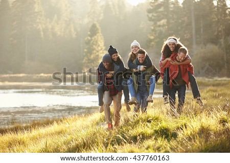 Six friends have fun piggybacking in the countryside by lake - stock photo