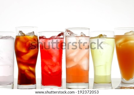Six glasses all containing different colored liquids lined up in a row. - stock photo