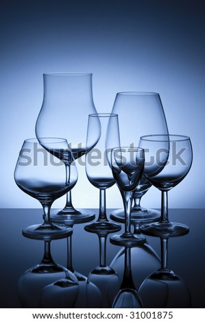 Six glasses on glass surface backlit with blue gelled flash - stock photo