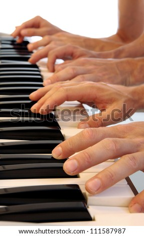 Six hands playing simultaneously on a grand piano with bright white background - stock photo