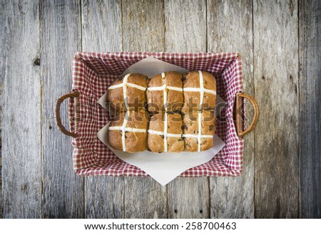six hot cross buns in basket on rustic wooden background - stock photo
