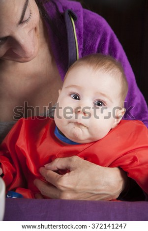 six months age blonde caucasian baby red bib in woman mother purple velvet jacket arms eating puree - stock photo